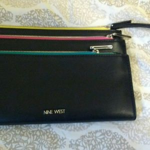 Clutch with wrist strap and three zippered pocket.